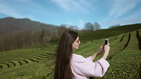 gigantikus : Shot from behind of cute brunette woman taking pictures on smartphone on gigantic plantation on mountains. Spending time enjoying nature.