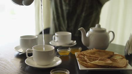 teacup : Man is pouring tea in a cups sitting at the table. Morning food. Pancakes and honey on the table.
