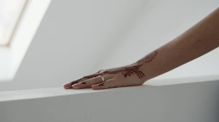 kružba : Close up shot of a womans hand decorated with henna traceries. Hand on a counter. Sun shines out of the window. White room.