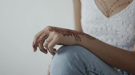 spletitý : close up shot of the womans hand, the lady has an engagement ring on her finger and a guard mehendi, the teenager has a natural manicure