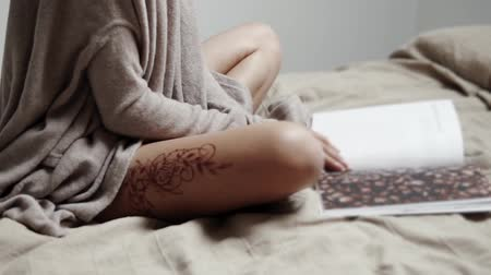 kadınlık : close up shot of the body of a woman who holds a fashion magazine in her hands, a lady with a henna tattoo on her leg flips through pages Stok Video