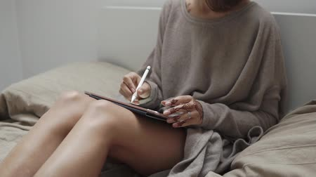 using stylus : Slim woman is placed in her tranquil room and drawing on a pad of mobile computer by stylus pen. She is relaxing in her holiday and engaging in the creative process