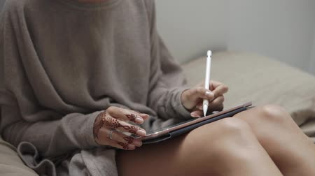 crayon couleurs : close up shot of the womans hands, the lady has on her hand a tattoo of henna, she is engaged in art drawing on a portable tablet, the artist is on the couch