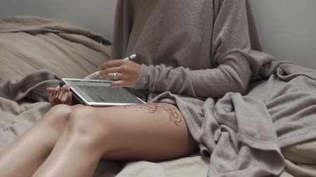 amulet : close up shot of a womans hands, a lady has a tattoo on her legs and a mandala on her fingers, she uses a pencil to view social networks through the intet