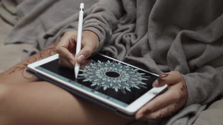 sto : close up shot of a womans hands, a lady draws a white flower on a portable tablet, a woman works as a graphic designer and draws a mandala in her room Dostupné videozáznamy