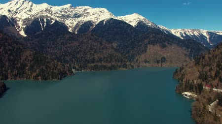 neobdělávaný : Aerial view of landscape with huge clear lake and mountains. Tops are covered by snow, and slopes are covered pineries, sun is shining bright