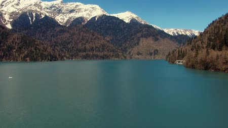 neobdělávaný : Aerial view over picturesque lake and mounts in sunny day. Camera is moving down to water, doing vertical panorama Dostupné videozáznamy