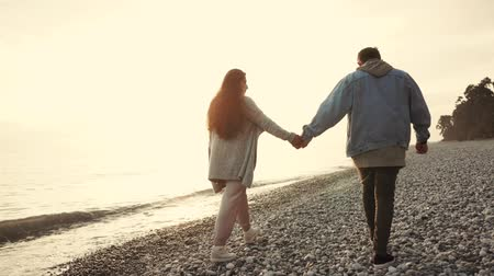 小石 : Man and woman are holding hands to each other and strolling on sea coast in evening. Loving pair is meeting sunset in romantic walking