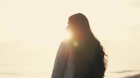 desolado : Pretty brunette is strolling alone on sea shore, watching sunset. She is touching her long dark hair and looking on horizon sorrowfully Stock Footage