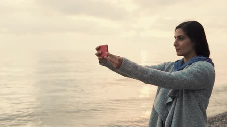 ona : Young brunette is taking pictures herself, using camera of mobile phone. She is posing near sea shore, on background of sea horizon with sunset