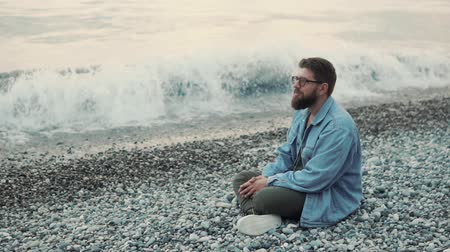 svetr : a young and bearded man sits on a stony beach in a wilder time, the jennelman enjoys the sea view and looks into the distance, the waves beat on the shore
