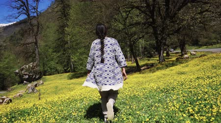 national park : a young woman walks the hilly terrain in interesting clothes, the lady walks on the flower floor in the summer, trees and shrubs are nearby