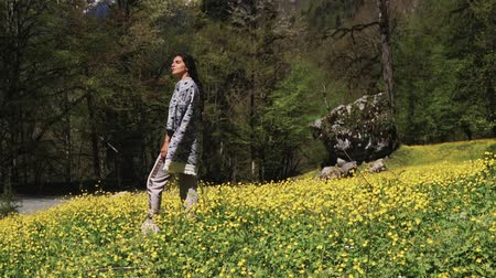 breathing fresh air : Brunette girl is relaxing, standing on a grass in blooming lawn. She is sniffing aroma of flowers and fresh mountains and forest air Stock Footage