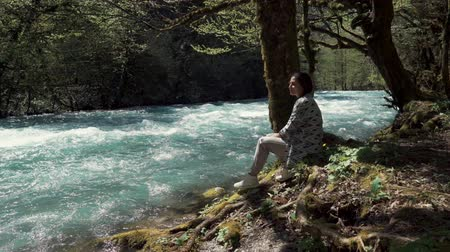 album de recortes : a young woman sits on an earthen bank near the swift river stream, a lady looks at the water and reflects on the meaning of life, she is in the park on a summer day Archivo de Video