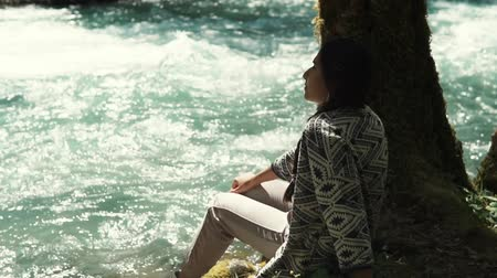 scrapbook : a young woman, went for a day walk to the park area, the lady sits by the river and a lonely tree, she looks at the swift flow of water Stock Footage