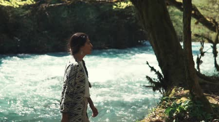 scrapbook : a young woman in stylish clothes comes to the river bed to sit by a lone tree, the lady is tired of looking like and wants to move in a park or reserved area