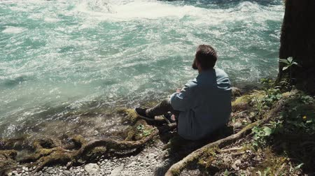 sobre : a young man is on the nature on a warm summer day, he looks at the stream of water, which makes you think about the eternal, the river is rapidly moving into the distance Vídeos