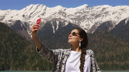 rochoso : young woman is taking photos on a mobile phone, the lady is on the background of snow-capped mountains in a beautiful nature reserve in the spring time