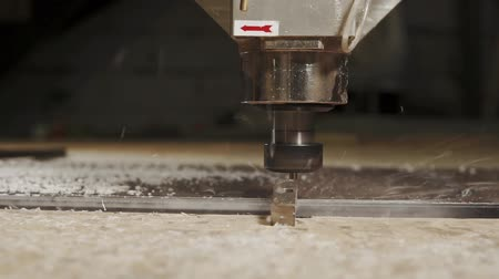 automatický : Cutting CNC tool is carving plastic in a workshop on plant. Close-up of saw and plastic chips flying around