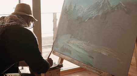 realista : the adult artist is engaged in professional drawing by oil paints, he puts a layer of color with a brush on the canvas that stands on the easel
