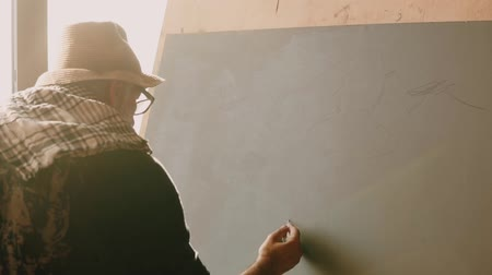 шедевр : an adult man is engaged in drawing, a pensioner is drawing a drawing of the mountains on the canvas during his retirement, the man enjoys the creativity