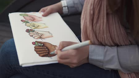car designer : Close up shot of a talented woman drawing in a sketchbook with markers. Fantastic bright drawing of hands with flowers. Great art.