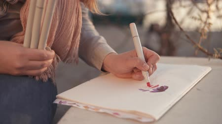 аксессуары : Close up shot of young girl coloring her drawing with markers. Talented inspirational woman doing sketches outdoor. Стоковые видеозаписи