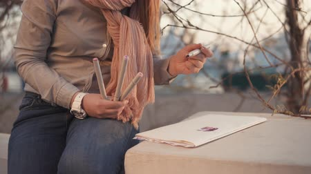 kütük : a close shot at a teenagers hands, one is engaged in drawing while walking in the park, the artist makes sketches and sketches of what she saw