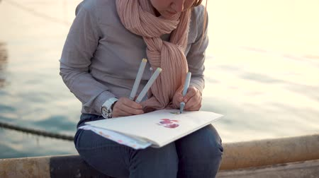 ona : a young woman holds colored pens in her hands and draws flowers, while waiting for her friends, she is near the water in the cool autumn season