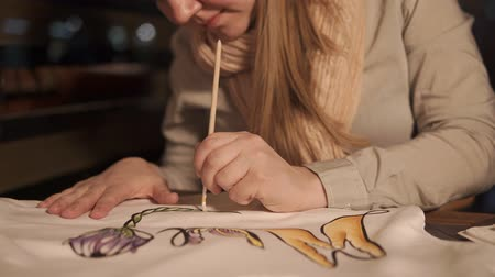 sem camisa : a young woman draws on a swit with watercolor paint and a brush, then she sells it in her workshop for decorating and creating fashionable clothes Stock Footage