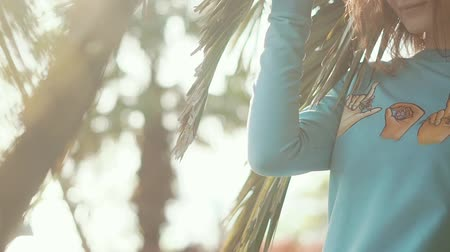 longhair : Portrait of a nice and beautiful woman coming from behind palm leaves. Adorable girl wearing stylish clothes in summer. Stock Footage