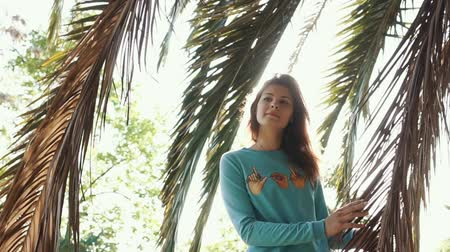 longhair : Attractive redhaired woman is standing under palm hiding from sun. Beautiful woman posing on vacationg wearing blue sweater. Stock Footage