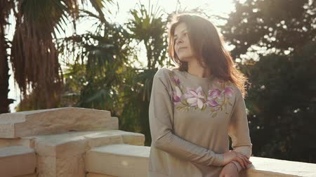 longhair : Portrait of a beautiful and affectionate young woman posing on the balcony. Woman is leaning on the handrails. Palm trees around. Stock Footage