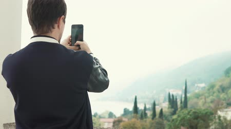 фотографий : Shot from behind of a tourist taking photos on smartphone out of the hotel. Beautiful landscape. Sea and mountains.