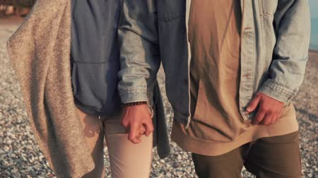 hour hand : Close up shot of a young couple strolling on the beach in the evening. Man and woman are holding hands. Enjoying the day. Stock Footage