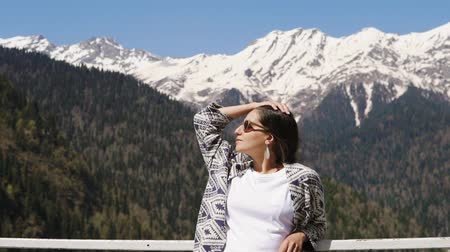 pontos : Portrait of wonderful brunette woman enjoying day outdoor in forest. Woman is posing with sunglasses on. Beautiful mountains on background.