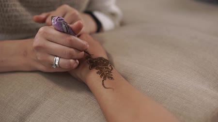 произведение искусства : Female master is painting floral ornaments on hand skin of woman. She is lying dye from tube, creating beautiful traditional eastern decoration, close-up Стоковые видеозаписи