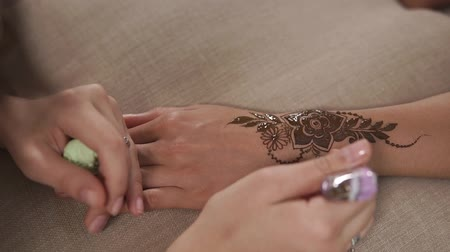 sanskrit : Detail shot of working of mehndi artist in salon. Woman is drawing floral decoration, applying henna dye on skin Stock Footage