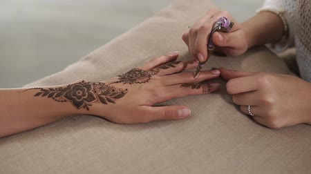 paszta : Close-up of hands of artist and customer during mehendi drawing in a salon. Female master is squeezing paste from tube and lying it on skin of girl