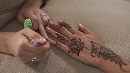 запутанный : close up shot of a womans hands, a tanned ladys hand has a mehendi for a wedding celebration, she prepares for a traditional holiday and has a charm