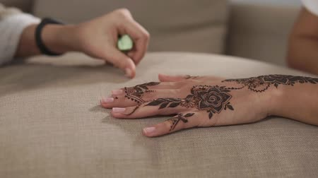 sanskrit : Master is showing for customer woman arabian mehndi patterns on skin. Close up of hands with beautiful brown ornament on body