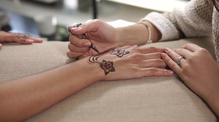 запутанный : close up shot of the master hands, the woman draws a tattoo with the help of henna at the hands of the visitor to the spa salon, the visitor wants to draw the amulet Стоковые видеозаписи