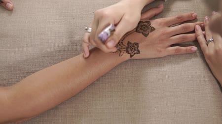хозяин : Master is drawing floristic pattern on skin of young model woman. Traditional arabian form of body art, trendy direction of beauty industry, close-up of hands