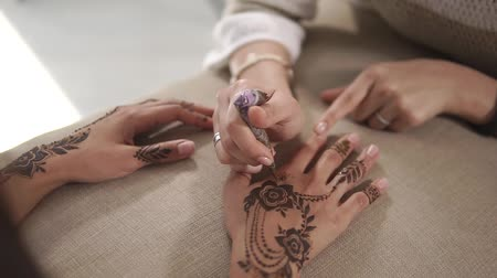 hinduizmus : Close-up of hands of two women in beauty studio in mehendi procedure. Master is covering skin by henna paste and client is holding both hands on pillow