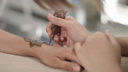 amulet : close up shot of the master hands, a woman draws a henna tattoo on the hands of a spa visitor, the lady is holding a tube with vegetable paint to draw patterns Stock Footage