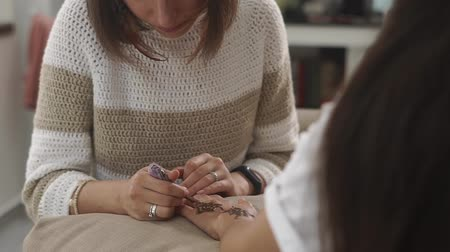 amulet : mehendi master paints the amulet at the hands of the visitor of the spa salon, the woman carefully displays the patterns on the tanned skin Stock Footage