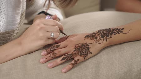 sanskrit : Adult woman is painting floristic patterns on hands of girl with tanned skin. She is using traditional henna paste for making temporary tattoo