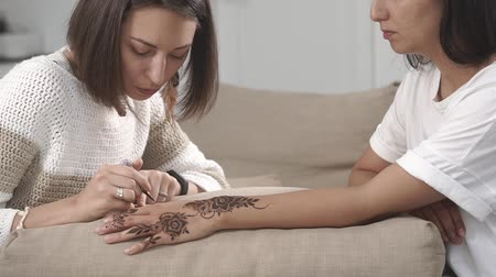 amulet : the make-up artist applies the paint to the skin of the hands of the spa visitor, she draws the mehendi, the lady likes to observe the creative process
