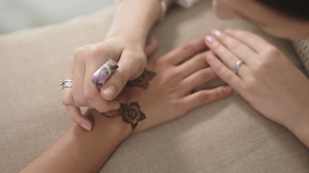 amulet : close up shot of a womans hands, a lady has a mehendi on her wrist and fingers, the master is busy drawing a tattoo using a paint called henna