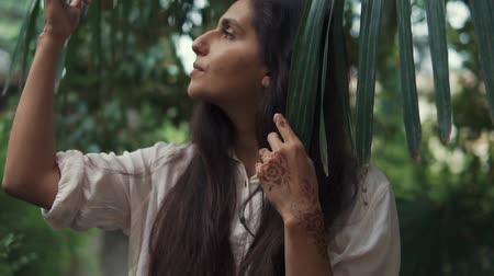 crochê : Close up shot of beautiful brunette woman with henna art on her hands posing by the palm tree with its leaves. Spending time outdoor on nature.